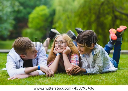 Smiling kids having fun at grass. Children playing outdoors in summer. teenagers communicate outdoor - stock photo