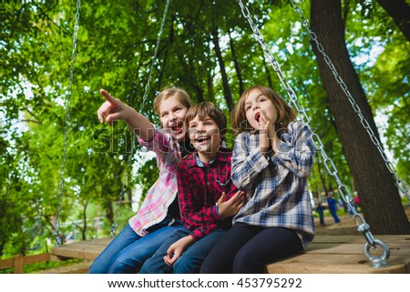 Smiling kids having fun at playground. Children playing outdoors in summer. Teenagers riding on a swing outside - stock photo