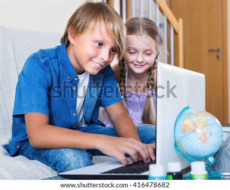 Smiling kids internet chatting on notebook indoors - stock photo