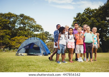 Smiling kids posing together during a sunny day at park - stock photo