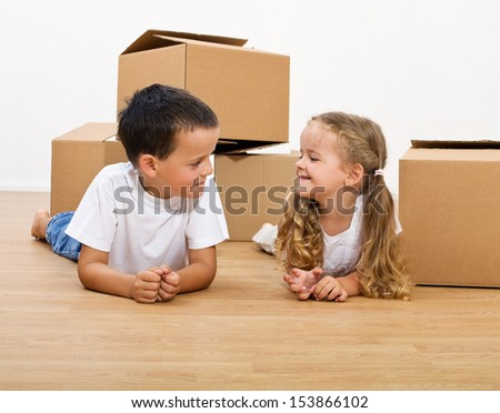 Smiling kids with cardboard boxes laying on the floor - stock photo