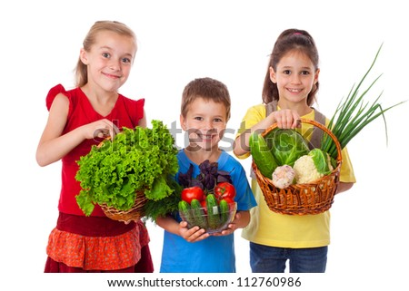 Smiling kids with fresh vegetables in basket, isolated on white - stock photo