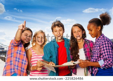 Smiling kids with map at city tours stand together - stock photo