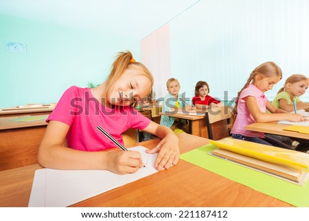 Smiling kids writing in classroom during lesson - stock photo