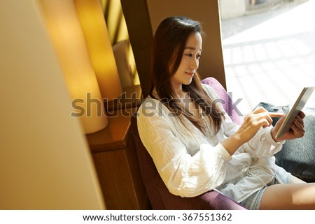 Smiling Korean woman sitting in armchair and using tablet computer