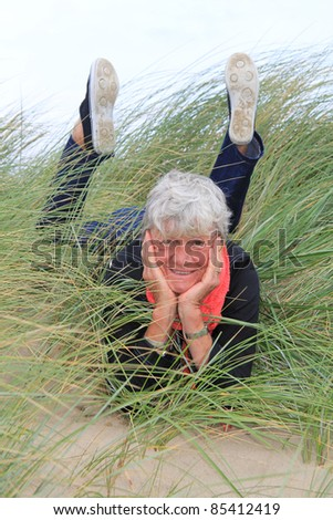 Smiling lady in her seventies laying down outside in the grass. - stock photo