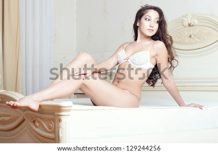 Smiling lady sitting and pamepring in bedroom - stock photo