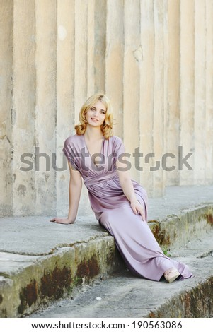 smiling lady  sitting near the columns - stock photo