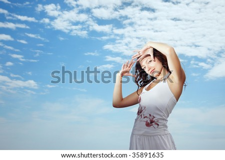 Smiling lady with hands at her face against cloudy sky