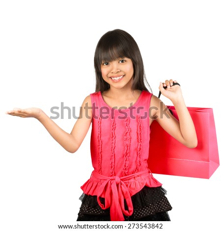 Smiling little asian girl hand up showing empty space on her hand with shopping bags, Isolated over white - stock photo