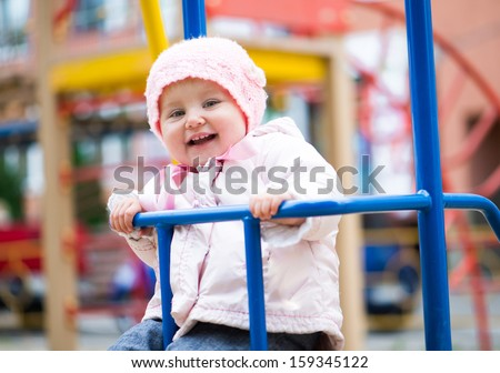 smiling little baby swinging at the park - stock photo