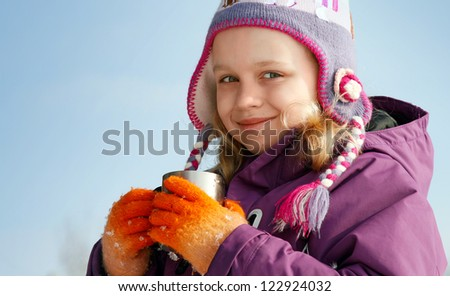 Smiling little blond girl in cold season wears winter outwear with metal thermos cup of hot tea - stock photo