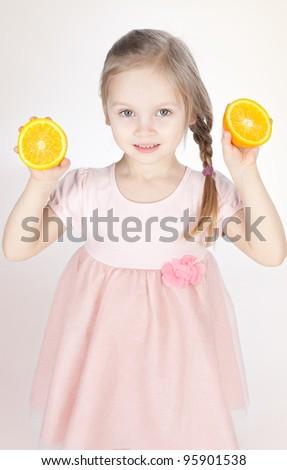 Smiling little blonde girl holding fresh oranges - stock photo