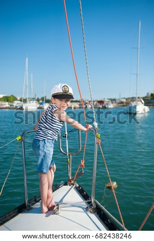 smiling little boy captain aboard luxury boat during the ocean cruise in sunny summer day