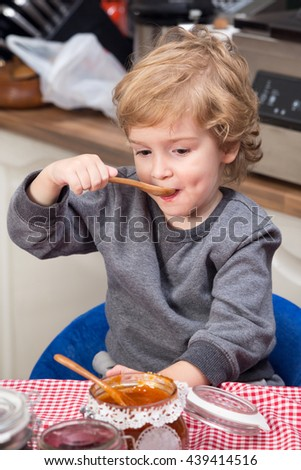 Smiling little boy eating apricot jam at the table.  - stock photo