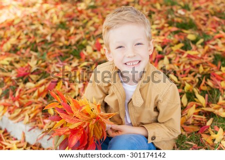 smiling little boy enjoying colorful autumn time in the park holding bouquet of fall leaves - stock photo