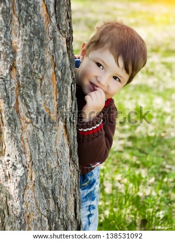 Smiling little boy hiding and peeking from behind a tree - stock photo