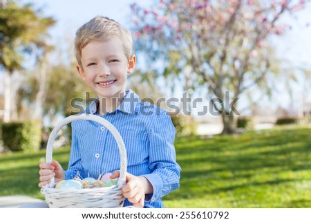 smiling little boy holding easter basket with eggs after egg hunt at spring time - stock photo