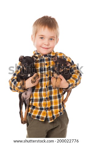 smiling little boy holding his puppies over white background - stock photo