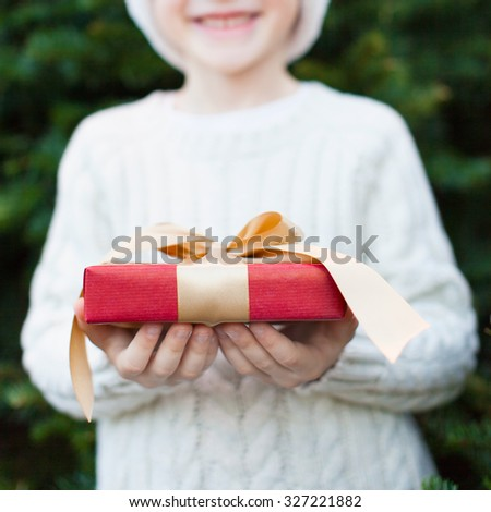 smiling little boy holding nicely wrapped christmas gift, shallow DOF - stock photo