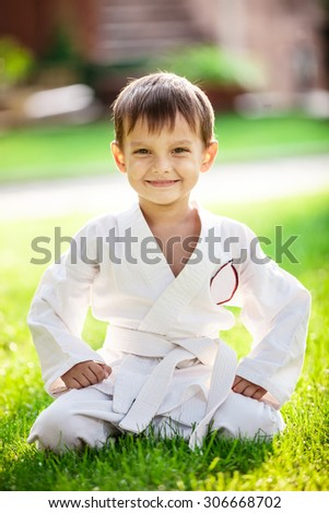 Smiling little boy in kimono sitting on grass in park - stock photo