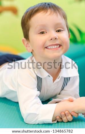 Smiling little boy in kindergarten - stock photo