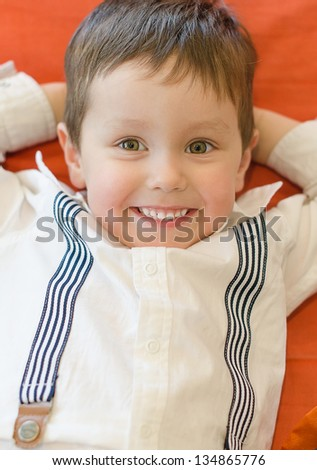 Smiling little boy lying with arms crossed - stock photo
