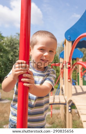 Smiling little boy on playground in summer - stock photo