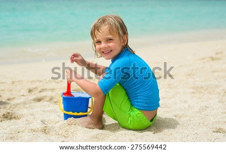 Smiling little boy plays in the sand at the beach