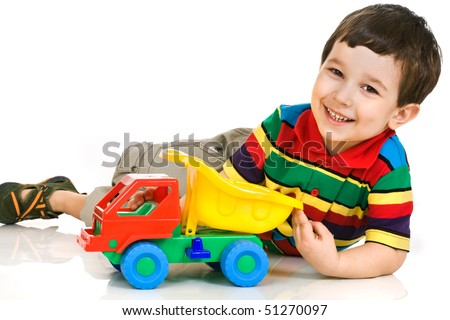 Smiling little boy plays with toy car - stock photo