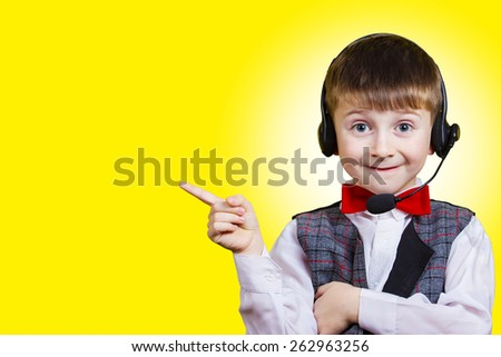 Smiling little boy pointing up at a copy space with phone headset  isolated on yellow background. Communication,Internet - stock photo