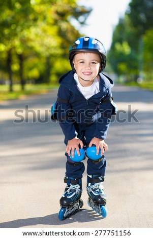 Smiling little boy rollerblading down the sidewalk - stock photo