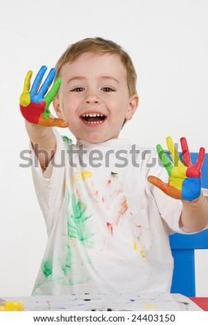 Smiling little boy show coloured hands - stock photo