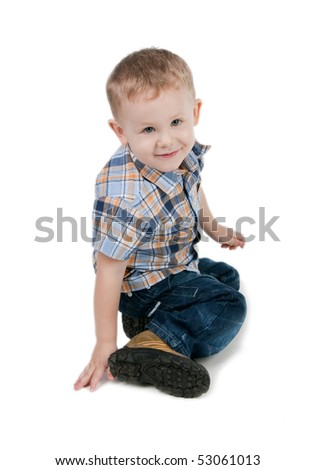 Smiling little boy sit on a floor, isolated on white - stock photo