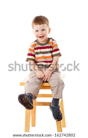Smiling little boy sitting on stool, isolated on white - stock photo