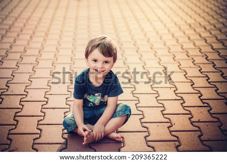 smiling little boy sitting on the ground and looking into the camera - stock photo
