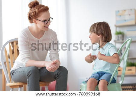 Smiling little boy talking with cheerful child psychotherapist during therapy session at office