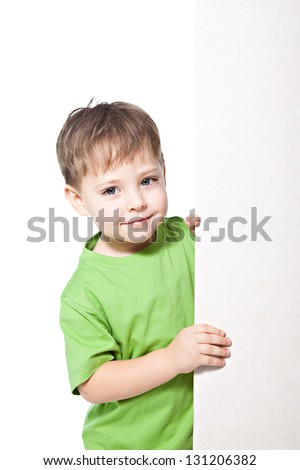 Smiling little boy with blank billdboard isolated on white background