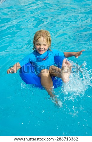 Smiling little boy with blue life ring has fun in the swimming pool