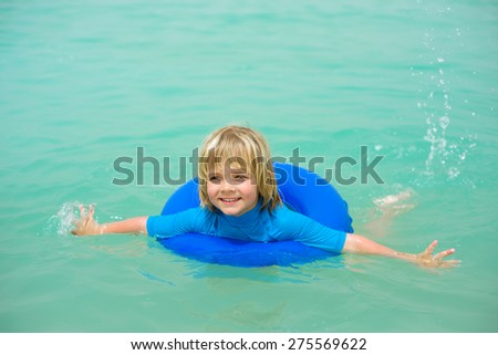 Smiling little boy  with blue life ring has fun in the water - stock photo