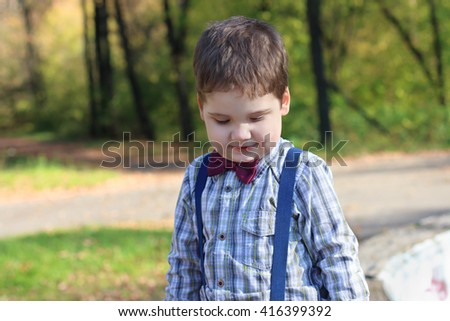 Smiling little boy with bow tie looks down in sunny green park  - stock photo