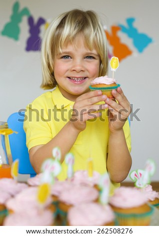 Smiling  little boy with cupcakes in Easter scene