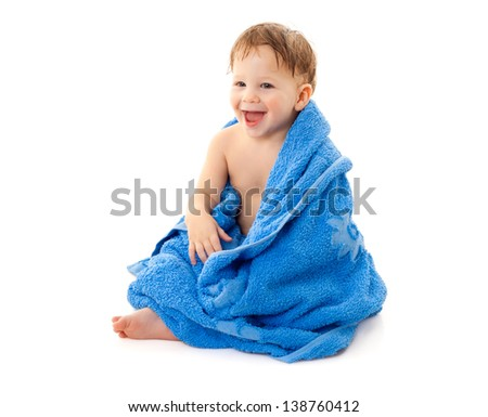 Smiling little boy with wet head sitting in the blue towel, isolated on white