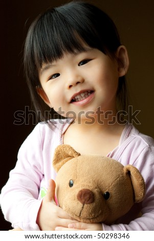 Smiling little child holding a teddy bear in her hand stock photo