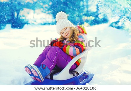 Smiling little child sitting on sled in winter day - stock photo