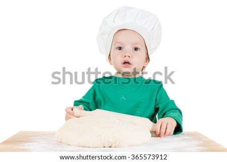 Smiling little cook boy kneading the dough for the cookies, isolated on white background.  Half-length portrait of the table in studio