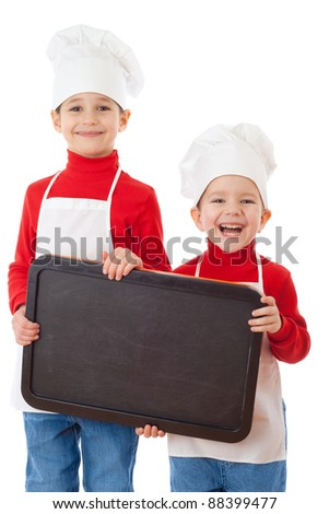 Smiling little cookers with empty chalkboard, isolated on white - stock photo