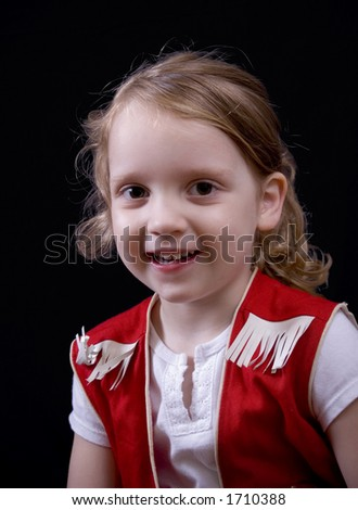 Smiling little cowgirl on a black background.