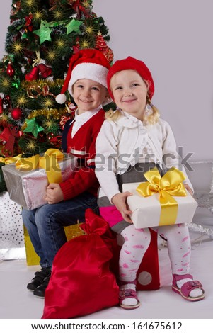 Smiling little girl and boy sitting with gift under Christmas tree - stock photo
