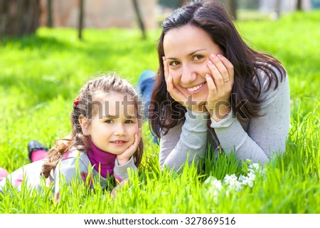 Smiling little girl and her mother having fun at park early spring. They lie on a bright green grass.